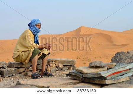 SAHARA DESERT, MOROCCO, JULY 12: Unidentified Berber man in the Sahara desert, Morocco, July 12, 2013. Berber people living in traditional lifestyle as a hundred years ago in the desert.