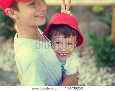 Happy carefree little boy showing donkey ear to younger brother outdoor summer holiday