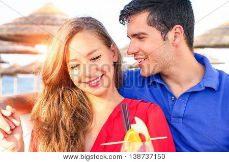 Beautiful couple in love flirting at sunset at beach bar resort - Man whispering in the ear of smiling girlfriend on tropical vacation day - Concept of romantic summer holiday and successful lifestyle
