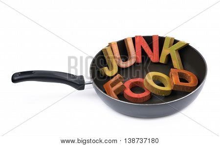 Words Junk Food made of colored wooden letters in a cooking pan, composition isolated over the white background