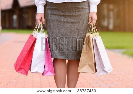 Close up of female legs standing on street. Woman is carrying many shop packets