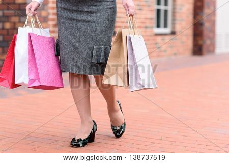 Close up of legs of mature lady going shopping in city. She is walking and holding colored packages