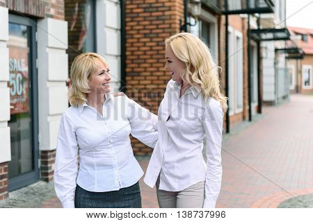 Joyful mother and daughter and standing and embracing outdoors. They are looking at each other with love. Women are talking and smiling