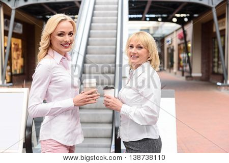 Happy mother and daughter are entertaining in shopping center. They are standing near escalator and holding cups of coffee. Women are looking at camera and smiling