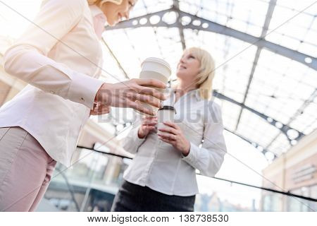 Low angle of two women drinking coffee and smiling. They are standing in shopping center