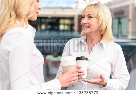Friendly mature mother and young daughter are talking with joy. They are drinking coffee while standing in shopping center. Women are smiling happily