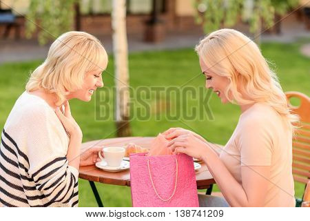 Happy young woman is making gift to her mother. She is taking clothing from packet and smiling. Senior woman is looking at cloth with admiration