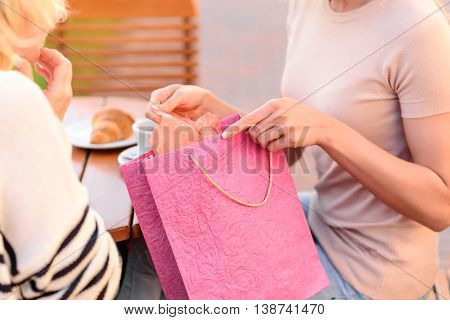 Close up of female hands holding package with colored clothing. Young woman is giving it to her mother. Lady is looking at packet with happiness. They are sitting at table in cafeteria