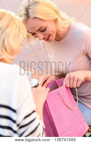 Joyful young woman is showing her mother a shopping packet. Mature lady is looking at it with interest and smiling. They are sitting in cafe