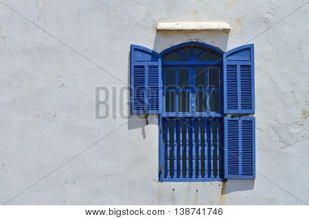 Traditional blue window on a withe wall, Morocco