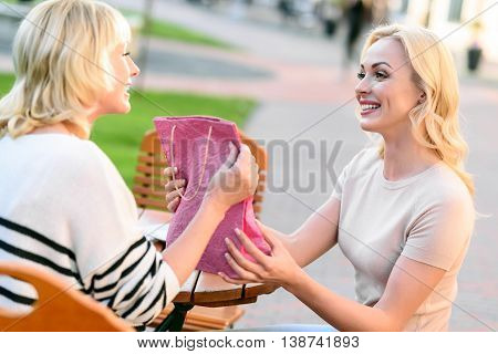 Happy birthday. Joyful young girl is giving packet gift to her mother. They are sitting in cafe and smiling