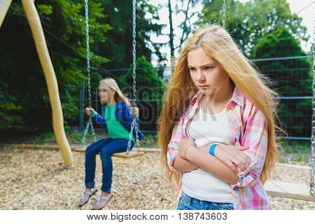 Portrait of offense child at park. On the background other girl riding a swing.