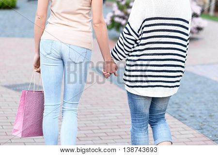 Close up of two women walking and holding hands. Young girl is carrying shopping packet. Focus on their back