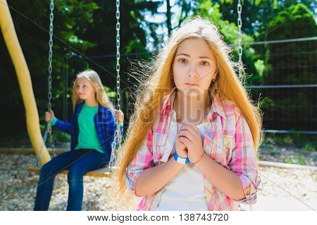Portrait handsome teen pleading or beging at park. On the background other girl riding a swing.
