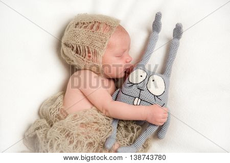 Sleeping Newborn baby hugging a stuffed rabbit