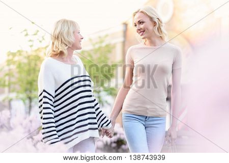 Happy daughter is walking on street with her parent. Women looking at each other with love and smiling. They are holding hands