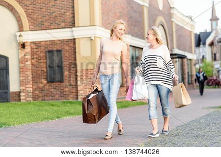 Joyful mother and daughter are going shopping together. They are walking on street and holding packets. Women are talking and smiling