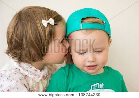 The girl whispers to the boy's ear a secret