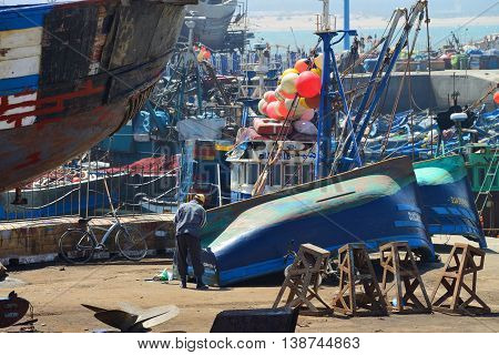 ESSAOUIRA - JULY 15: Unknown man repairing boat in harbor of Essaouira, Morocco, July 15, 2013. Essaouira is one of the most popular tourist place on Atlantic coast in Morocco.