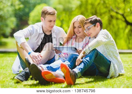Smiling kids having fun and look to the tablet at grass. Children playing outdoors in summer. teenagers communicate outdoor.