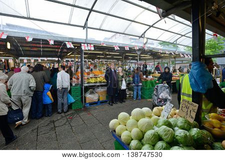 BIRMINGHAM, ENGLAND - JUNE 13: Unknown man trades a fruits in Bull Ring market on June 13, 2013 in Birmingham, England. Birmingham's outdoor Bull Ring market sees over six million shoppers every year