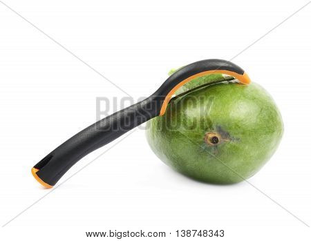 Ripe green mango fruit and peeler tool knife composition isolated over the white background