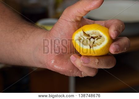 Squeezed fresh yellow lemon on hand. Close Up