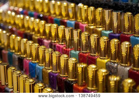 Many nail polish multicolor bottles arranged in rows background. A lot of different colors nail varnish in a shop display