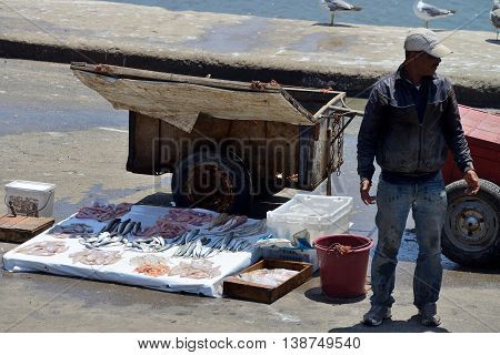 ESSAOUIRA - JULY 15: Unknown man sell fresh fish in harbor of Essaouira, Morocco, July 15, 2013. Essaouira is one of the most popular tourist place on Atlantic coast in Morocco.