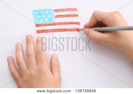 Child's hands drawing American flag on paper