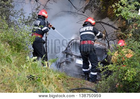 TULCEA, ROMANIA - JUNE 11: Danube Delta Rally special trial windfarm on June 11, 2016 in Tulcea, Romania; car on fire and firemen trying to estinguish fire