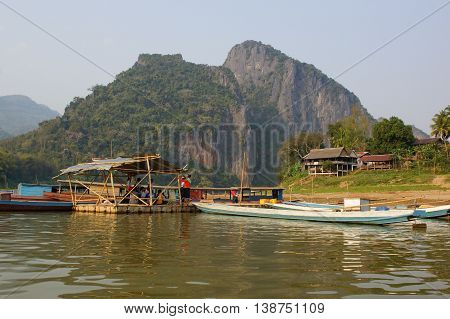 LUANG PROBING DISTRICT, LAOS - FEBRUARY 15, 2016: People waiting on the Ferry during sunset on February 15, 2016 in the Luang Prabang district, Laos, Asia