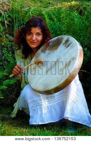 beautiful shamanic girl with shaman frame drum in the nature