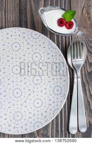 Grey empty plate with fork spoon and sauceboat on wooden background vertical top view