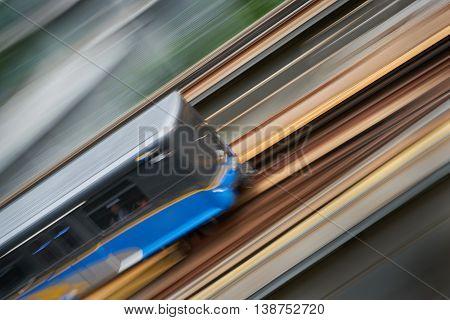 Urban Commuter Rail. An elevated commuter rail car speeds along a track. Motion blur.