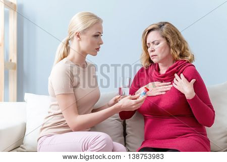 Mature woman is suffering from pain in heart. Her eyes are closed with despair. Her daughter is giving her pills and water. She is sitting on sofa and looking at mother sadly