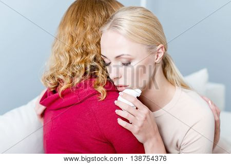 Depressed woman is crying with frustration. Her mother is embracing her and calming down. Female eyes are closed with trust