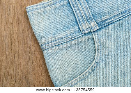 Close up of blue denim jeans on wooden background.