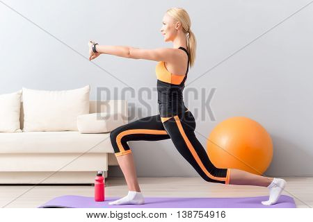 Fit girl is training her body at home. She is kneeling and stretching arms forward with smile