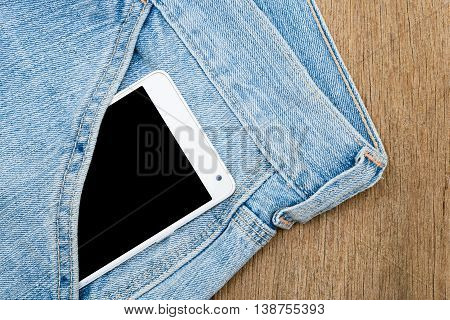 White smart phone in jeans pocket on wooden background.