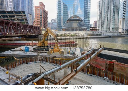 CHICAGO, IL - MARCH 31, 2016: Caterpillar excavator transferring gravel from barge in Chicago.  Chicago is the third most populous city in the United States.