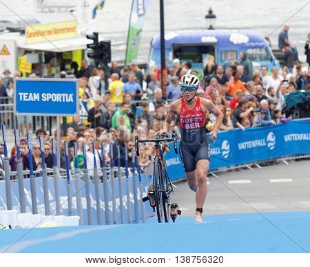 STOCKHOLM - JUL 02 2016: Leading triathlete Flora Duffy running with cycle in the transition zone in the Women's ITU World Triathlon series event July 02 2016 in Stockholm Sweden
