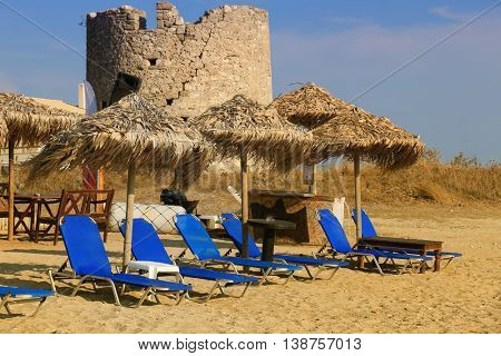 Straw umbrellas and sunbeds on a sandy beach in Greece.