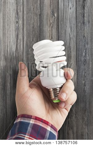 Energy saving lamp in the man's hand on dark wood background closeup. With clipping path