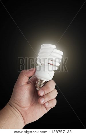 Energy saving lamp in the man's hand on black background closeup. With clipping path
