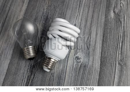 Energy-saving lamp and incandescent bulb on wooden background. Sales of light bulbs. Advertising on lighting technology.