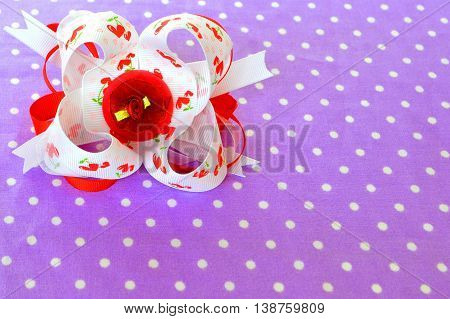 Bright bow of ribbon on fabric background with copy space. Beautiful accessory for girls. Hair decoration