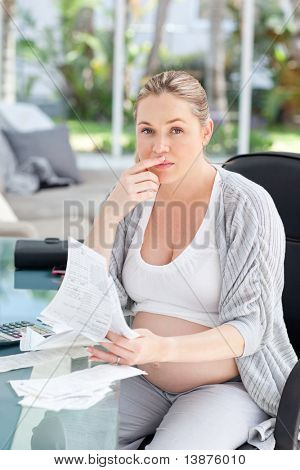 Worried pregnant woman calculating her domestic bills at home