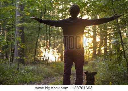 Rear view on single adult man with open arms in front of sun rising through trees of forest with his dog next to him.