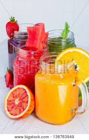 Vivid fresh smoothy drinks in glass jars with igredients on white table close up